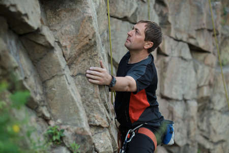 tenacious: Male rock climber clings to a cliff