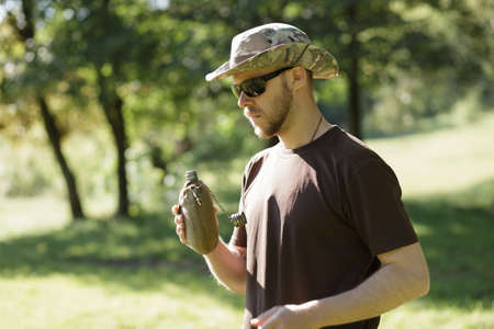 or thirsty: Hiking concept. Thirsty man having break drinking a flask of water. Foto de archivo