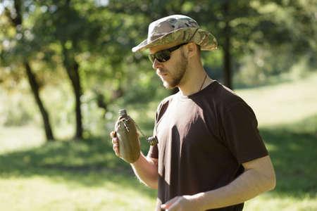 sediento: Senderismo concepto. hombre sediento que tiene descanso para beber una botella de agua.