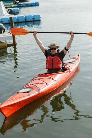 river scape: Portrait of happy waterman on river. He lifted up paddle.