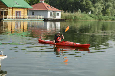 water scape: Man boating in red canoe at river pier at summer day Stock Photo