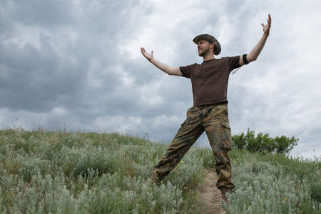 hands raised sky: Freedom man raised hands in field at moody sky background