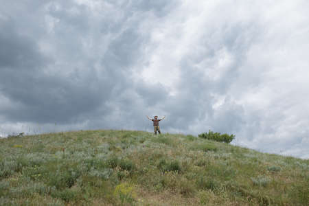 manos levantadas al cielo: La libertad del hombre levant� las manos en el campo en el fondo del cielo cambiante