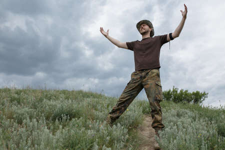 moody sky: Freedom man raised hands in field at moody sky background