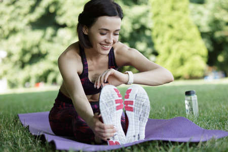 Sporty woman sitting on mat in park and look at watch