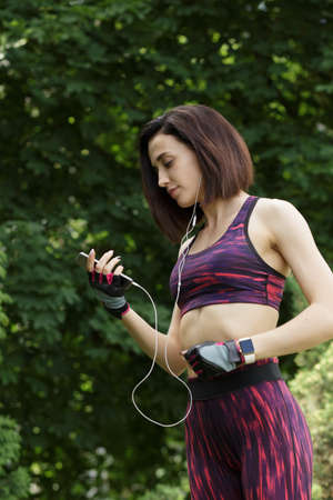 medium shot: Attractive sports woman listening to music in park