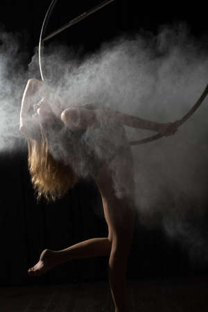 ring flash: Professional acrobatic woman on aerial hoop with flour Stock Photo
