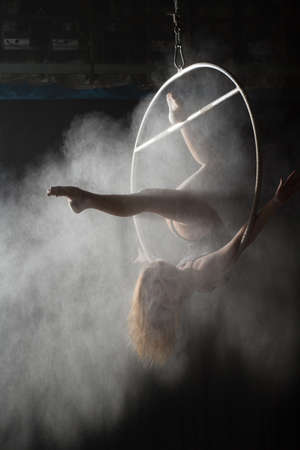 acrobat: Female acrobat doing gymnastic element on aerial hoop with sprinkled flour Stock Photo