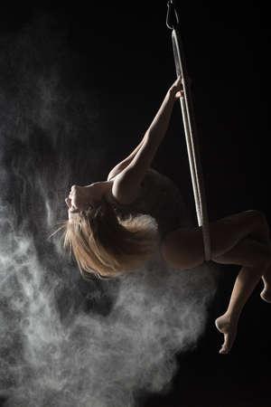 acrobat: Female acrobat doing element on aerial hoop with sprinkled flour