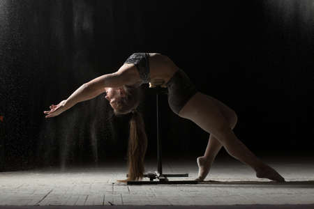 farina: Woman doing gymnastic element on stand while sprinkled flour