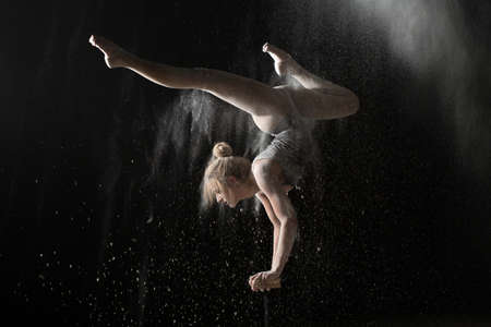 handstand: Gymnastic flexible woman handstand on equilibr at sprinkled flour Stock Photo