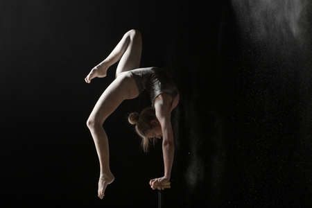 Woman gymnast handstand on equilibr at black background Stock Photo
