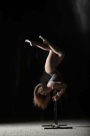 handstand: Woman gymnast handstand on equilibre at black background