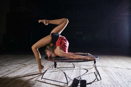 contortion: Flexible graceful woman doing artistic contortion on scene Stock Photo