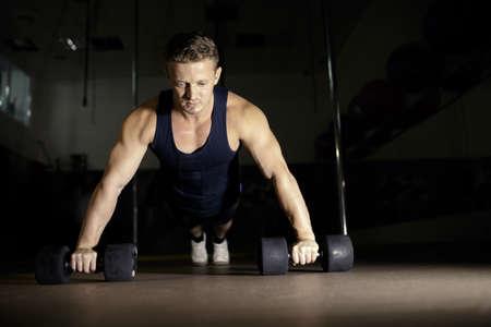 Young man doing pushups in gym