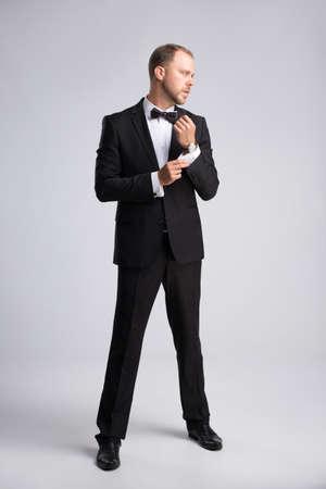 cufflink: Handsome young businessman buttoning cufflink on gray background Stock Photo