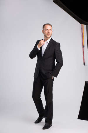 Stylish businessman in classic suit photoshooting in studio