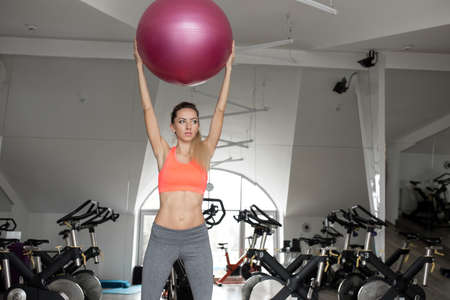 fitball: Woman doing a side stretching exercise using fitball in fitness studio Stock Photo