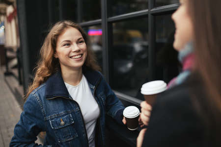 Two young women are happy to drink coffee in city. They holding a paper cups and smiling.