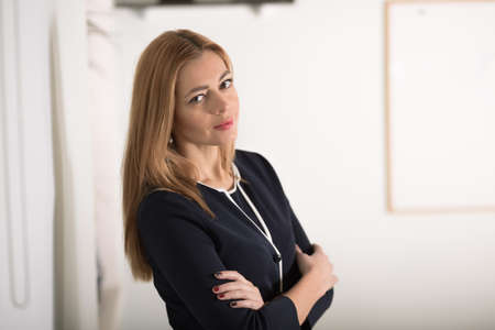 confidently: Adult caucasian businesswoman looking confidently at camera in workplace