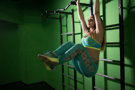 body built: Strong woman make exercise for abdominal muscles in gym