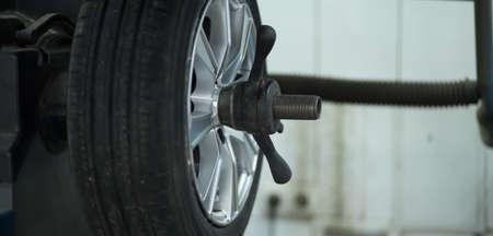 wheel balancing: Tire service. Mechanic balancing a car wheel on automated machine.