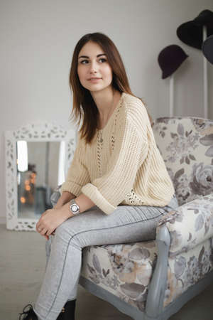 Lovely woman sitting on armchair