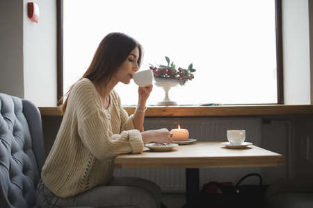 cosily: Lovely woman drinking cup of coffee in a cafe