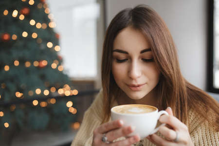 cosily: Lovely woman blowing on cup of coffee in a cafe Stock Photo