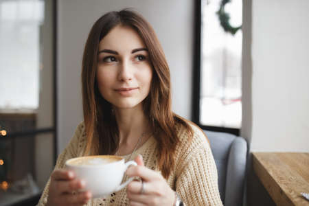 cosily: Woman sitting with cup of coffee in a cafe and look at window