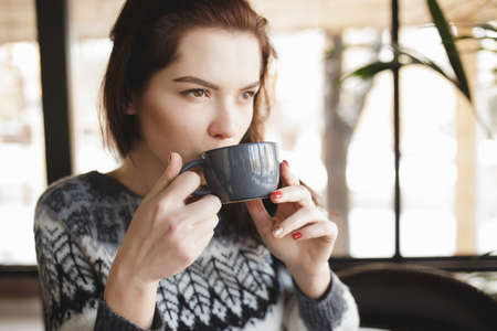 cosily: Woman drinking cappuccino in a coffee shop Stock Photo