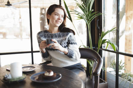 cosily: Woman in pullover snacking sweets in a cafe