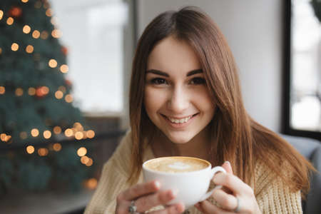 cosily: Lovely woman keep cup of coffee in a cafe