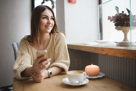 cosily: Cute woman using her smartphone in a coffee shop
