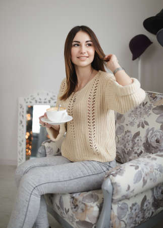 cosily: Lovely woman sitting on armchair with cup of cappuccino