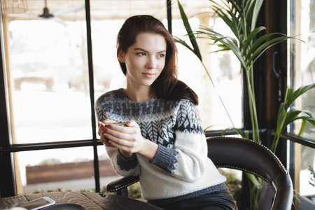 cosily: Woman in pullover sitting with cup of coffee in a cafe and look at window