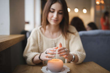 cosily: Woman warming hands above candle