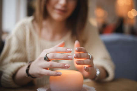 cosily: Woman warming hands above candle - cropped shot