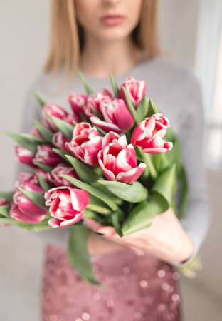 Cropped shot of unrecognizable woman holding bouquet of tulips