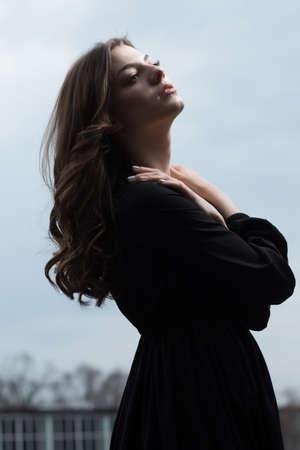 Beautiful woman in black dress against sullen sky background