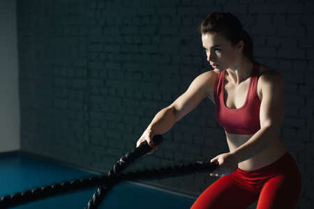 Strong woman make exercise with battle rope in functional training gym