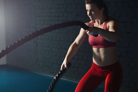 Woman make exercise with battle rope in functional training gym