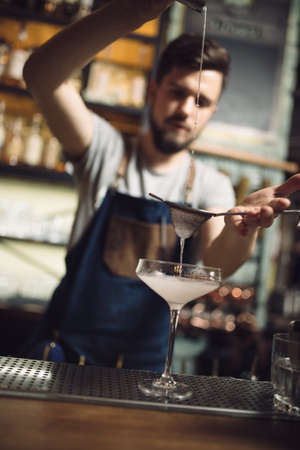 percolate: Young male bartender preparing an alcohol cocktail at a bar counter, he percolating juice Stock Photo