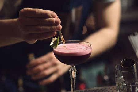 enhancer: Cropped of bartender preparing an alcohol cocktail at a bar counter - add flavor enhancer Stock Photo