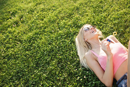 giggling: Pretty happy woman blowing bubbles in park, she enjoy summer holiday Stock Photo