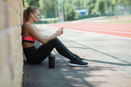 Young sporty woman athlete in sportswear sitting, listen music with headphones and relaxing on stadium track after hard workout Stock Photo