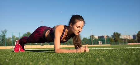 Jonge gelukkige sportvrouw in sportkleding die plankoefening op het gebied van het stadiongebied in openlucht maken. Gezond levensstijlconcept, sportactiviteit.