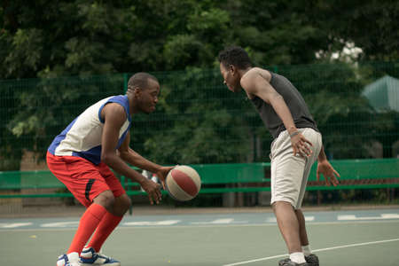 African american man friends playing on basketball court. Real authentic activity. Stock Photo