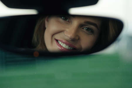 Beautiful woman looking to her face in rearview mirror of her car Banco de Imagens