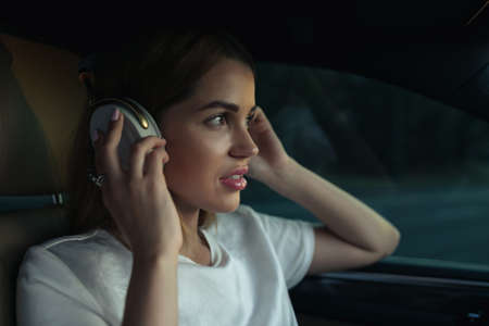 Luxury woman listen music with headphones in her comfortable car